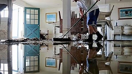 Man cleaning flooded home